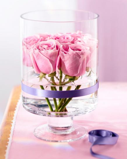 Nontraditional vase  Show off your beautiful blooms in a new way. Cut rose stems to 6 inches and remove leaves. Pack tightly in a straight-sided container and wrap with ribbon. Change the water daily.