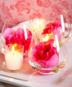 Candles and flowers  Easy centerpiece: Three stemless wine glasses hold roses floating in a bit of water, while votives provide a flickering accent.