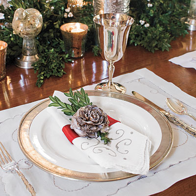 Make Your Own Napkin Rings  Make your own custom napkin rings by spray-painting cedar roses (the opened cones of the deodar cedar tree) silver and gluing them atop 2-inch-wide red ribbon. Tuck in a sprig of boxwood for an extra flourish.