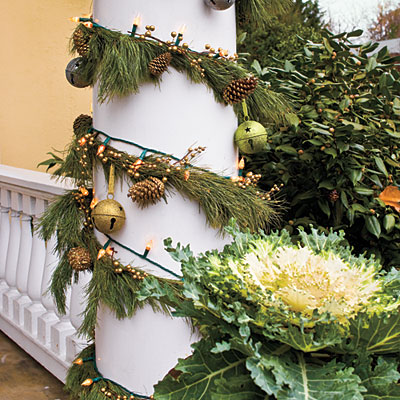 String Lights and Greenery  Disguise unsightly wires from string lights by winding them around a column or post with Christmas greenery or garland and setting a pretty container of ornamental cabbage or kale at the base