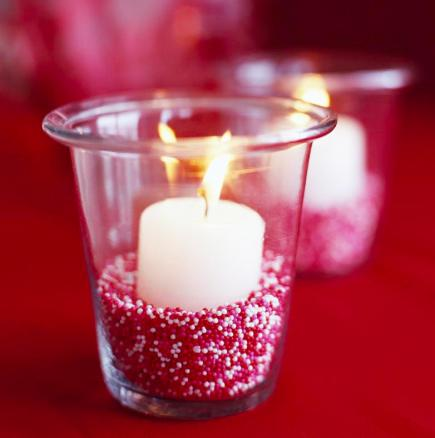 Festive candle  Add Valentine's candy nonpareils in the bottom of a votive for a festive candle display. Small glass beads from a crafts store will give a similar look.