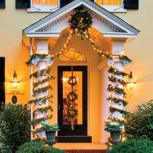 Wrap Columns with Garland  Play up the architecture of your home by accentuating features, like the stately columns flanking this front porch, with spiraling garland and bright Christmas lights.