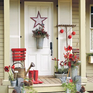 Greet with a Garden Theme  Convey a cozy welcome with a garden-inspired holiday decorating theme. Rustic aluminum containers on the door, porch, and stairs offer casual Christmas appeal when filled with herbs and bright accents, such as red amaryllis blooms and berries.