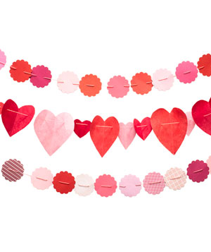 "Paper Garland Strands The kids might be sick of making paper snowflakes, but they're sure to rally behind these new shapes and colors.  What you need: Assorted Paper Needle and Thread 2"" Scalloped Shaped Hole Punch  Fold 3"" to 6"" paper squares in half and cut a half heart from the fold. Thread needle and string hearts together through the top center of the folded paper hearts. Using scalloped hole punch, make shapes from paper. Thread needle and string through the opposite sides of each scalloped paper. Add as many hearts and scallops as it takes to raech your desired length."