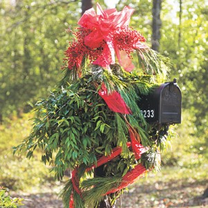 Drape Your Mailbox  Wrap sheer ribbon loosely around a pine garland and drape the garland around the mailbox. Wire clusters of bright nandina berries to the top of the post, and finish with a big bow for an eye-catching Christmas flourish.