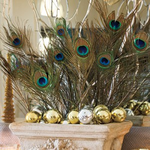 Make a Statement with Peacock Feathers  Use peacock feathers in lieu of traditional holiday flowers for a mantel that makes a statement. When paired with mirrored ornaments and curly willow branches they add just enough color to complement the Christmas tree.