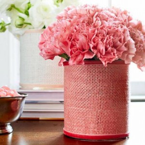 Wrap a vase  Create a pretty centerpiece by adding the texture of burlap to a plain cylinder vase and filling your vase with flowers in a matching color.  Wrap the vase with colored burlap, attaching with double-sided tape. Add ribbon to the top and bottom of the burlap with fabric glue.