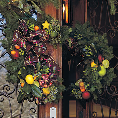Try a Two-Piece Wreath  Consider using a two-piece wreath to adorn a double-door entry. Start with a wreath that has a sturdy base so it will hold its shape. Fresh evergreen was used here, but a grapevine wreath will work just as well. Cut the wreath in half lengthwise with sturdy wire clippers. Use florist wire to attach evergreen clippings, fruits, and ribbons. Securely hang half of the wreath on each door so the two meet in the center when the doors are closed.